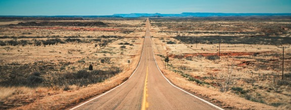 Long straight desert road stretching into the distance to the ho